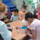 Kinder und Save me Betreuerinnen in Räumen der Save me Kinderbetreuung beim Basteln