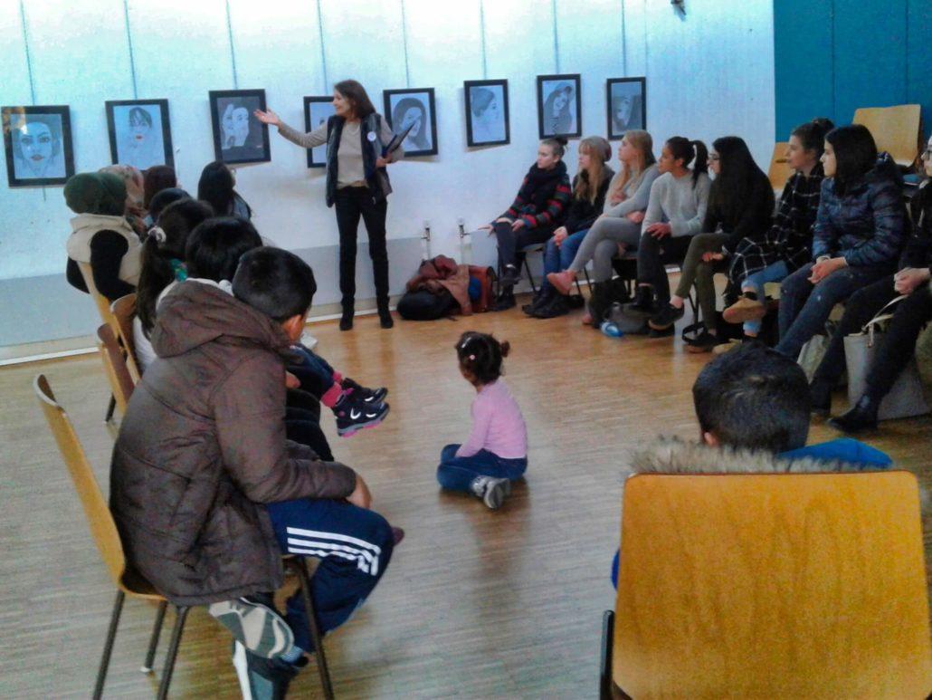 Eine ehrenamtliche Vertreterin von Save me Konstanz e.V. erläutert den SchülerInnen und geflüchteten Familien die aktuelle Ausstellung im Save me Treff
